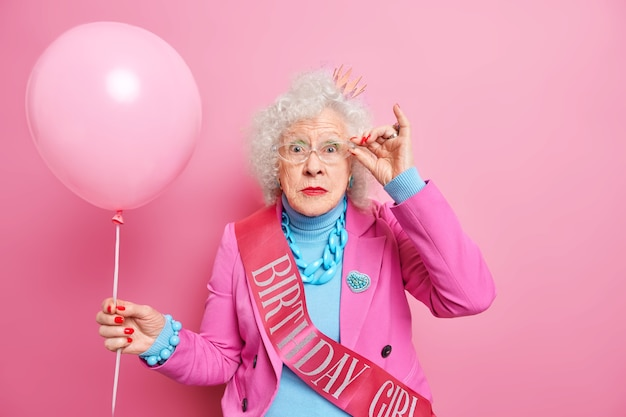 Photo of wondered wrinkled woman keeps hand on rim of spectacles, dressed in fashionable outfit holds inflated balloon celebrates birthday