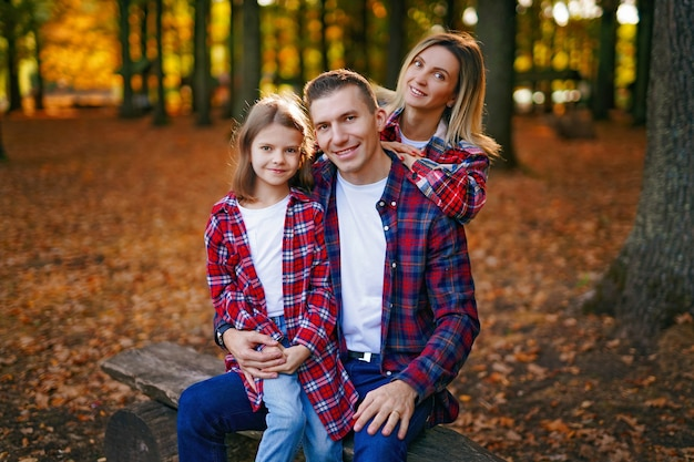 Photo of a wonderful family in the autumn forest on a bench