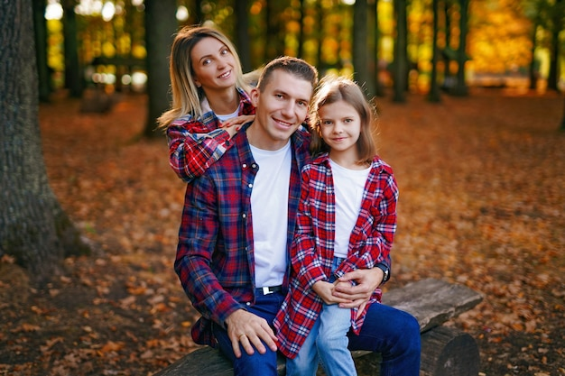 Photo of a wonderful family in the autumn forest on a bench.