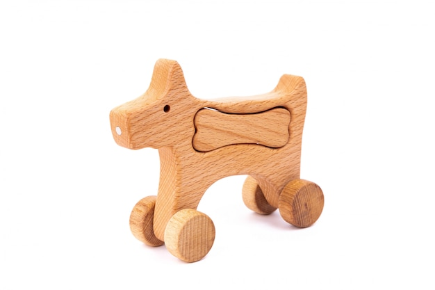 Photo of a wooden dog with bone on wheels of beech.