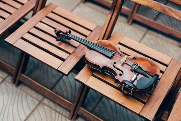 Photo of wooden violin on chairs.