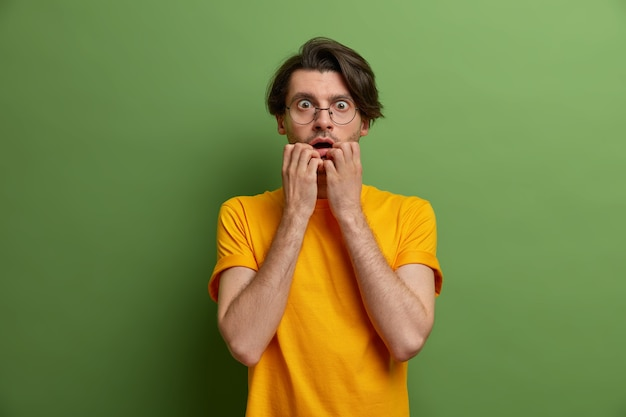 Photo of worried nervous man bites finger nails and stares with scared expression, frightened by something terrifying, wears round spectacles and yellow t shirt, poses against green wall