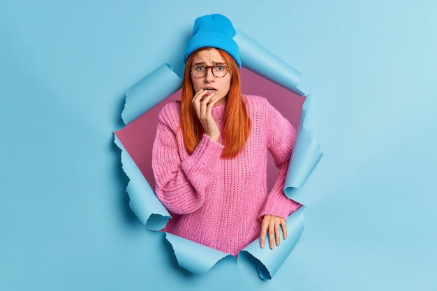Photo of worried redhead millennial woman looks scared stands anxious wears blue hat knitted sweater breaks through paper hole