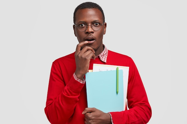 Photo of worried thoughtful confused black man carries notes, keeps hand near mouth, looks in bewilderment, wears casual clothes