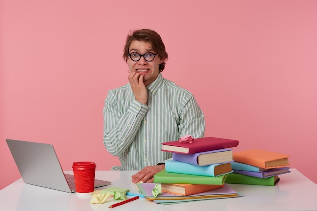 Foto del giovane ragazzo impaurito con gli occhiali, si siede al tavolo e lavora con il laptop, rosicchiando le dita, guardando a porte chiuse con espressione spaventata, isolato su sfondo rosa.