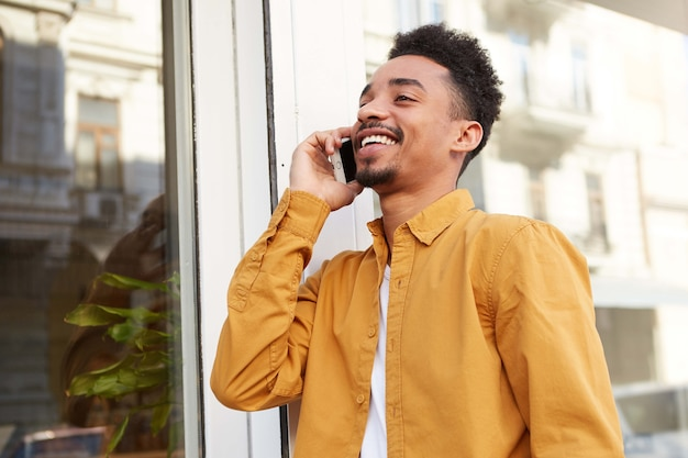 Photo of young african american glad man, walking down the street and talking on the phone with his friend, laugting and enjoying the day.