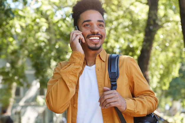 Photo of young african american glad man, walking at the park and talking on the phone with his friend, laugting and enjoying the day.