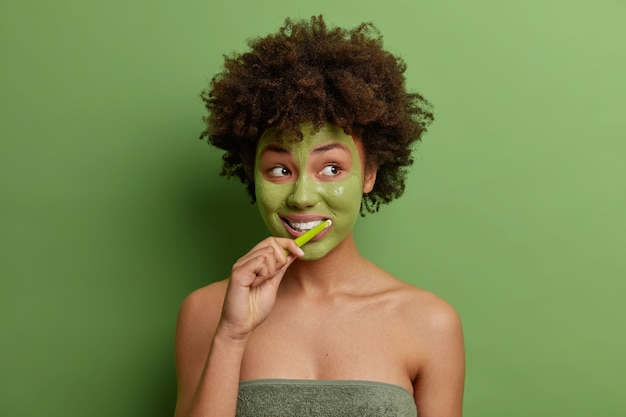 Photo of young african american woman applies green face mask brushes teeth uses tooth brush