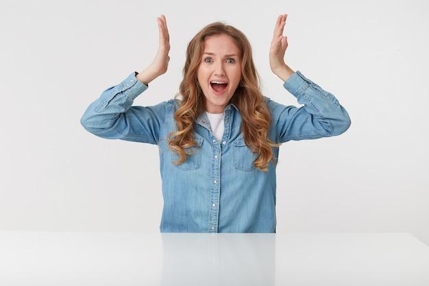 Foto di giovane donna bionda aggressiva indossa in camicia di jeans, urla e sembra arrabbiata con le mani alzate, seduto al tavolo bianco su sfondo bianco.