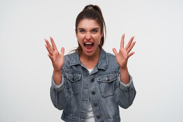 La foto della giovane signora bruna aggressiva indossa una maglietta bianca e giacche di jeans, urla e sembra arrabbiata con le mani alzate, si erge su sfondo bianco.