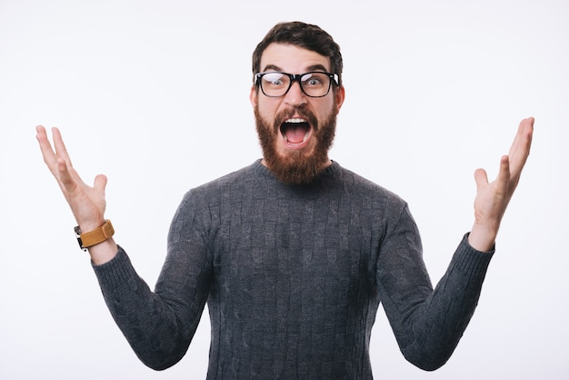 Photo of young amazed man gesturing over white background