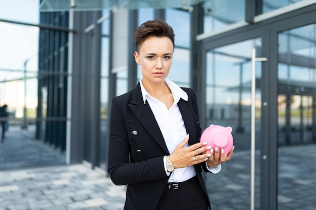 Photo of a young ambitious businesswoman on the background of a modern office building