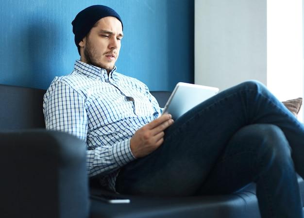 Фотография молодого и талантливого финансового менеджера, работающего с новым проектом. красивый мужчина, работающий в своем домашнем офисе. анализируйте бизнес-планы на ноутбуке.