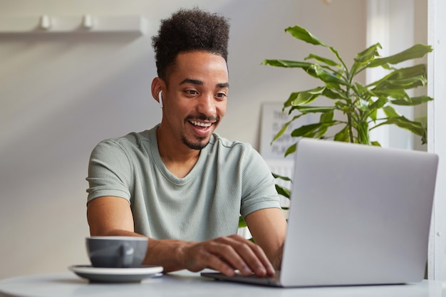 Photo of young attractive african american joyful boy,works at a laptop sits in a cafe , looks at the monitor and broadly smiling, chating with his girlfriend.