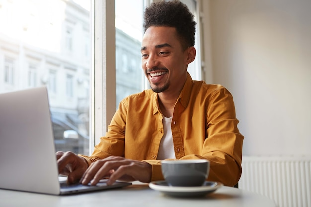 Photo of young attractive african american smiling boy, sits in a cafe, works at a laptop and drinks aromatic coffee, chatting with his girlfriend and enjoy freelance work.
