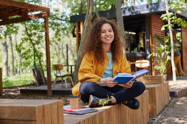 Photo of young attractive dark skinned curly student lady preparing for exam, siting on a cafe terrace, wearing in yellow coat, drink coffee, smiles broadly, enjoys studying.