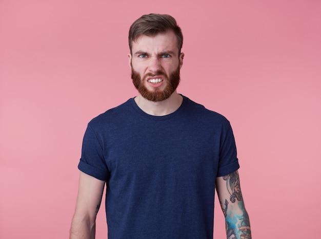 Foto di giovane uomo barbuto rosso diabolico attraente in maglietta vuota, sembra aggressivo e pazzo, si leva in piedi su sfondo rosa e scopre i denti.