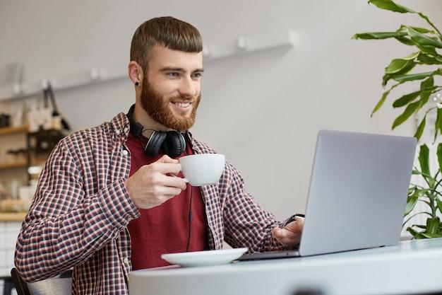 Foto di un giovane uomo barbuto attraente che indossa abiti di base, lavora a un laptop mentre è seduto in un bar, beve caffè, sorride ampiamente e si gode il lavoro.