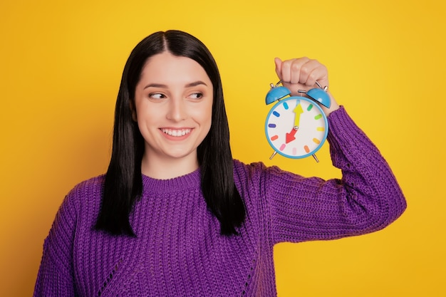 Photo of young attractive girl happy positive smile look clock alarm timer deadline isolated over yellow color background