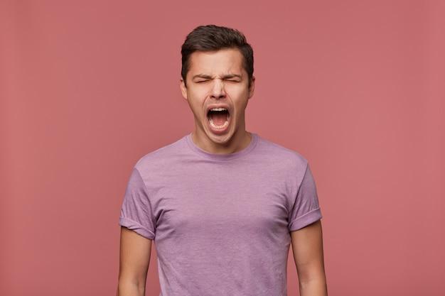 Foto di giovane ragazzo attraente in maglietta vuota, si erge su sfondo rosa con gli occhi chiusi e urla, sembra arrabbiato e infelice.