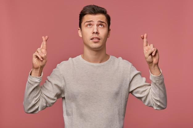 La foto del giovane ragazzo attraente indossa una manica lunga vuota, esprime un desiderio, spera in buona fortuna con le dita incrociate, guarda in alto per copiare lo spazio sopra la sua testa, isolato su sfondo rosa