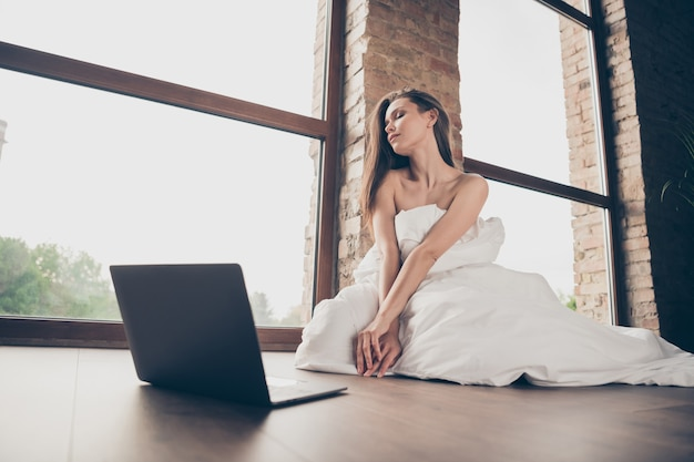 Photo of young attractive lady quarantine stay home covered white blanket naked shoulders sensual beauty talking notebook undressing boyfriend video call sit floor living room indoors