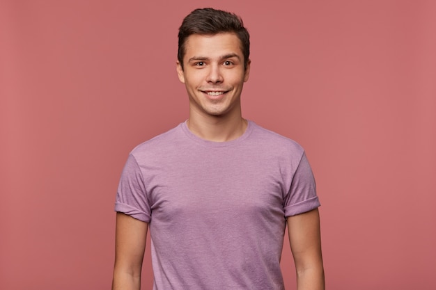 Photo of young attractive man in blanc t-shirt, cheerful looks at the camera, stands over pink background and smiles.