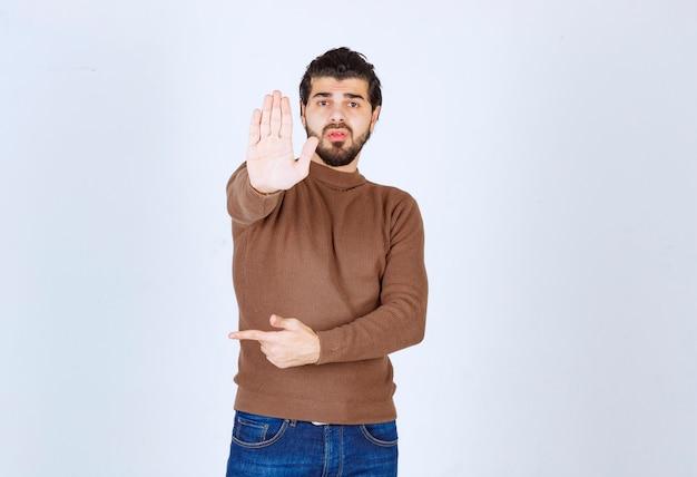 Foto di un modello di giovane uomo attraente che punta lontano e mostra il segnale di stop. foto di alta qualità
