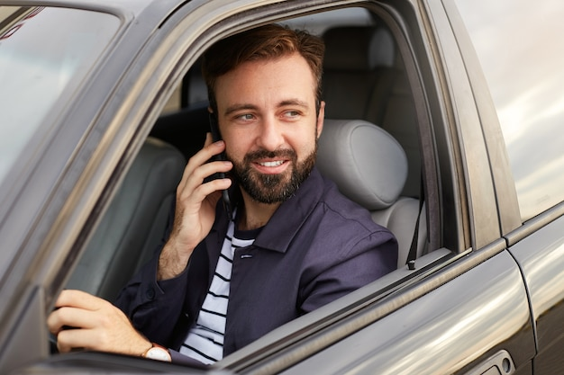 Photo of of young attractive successful bearded man in a blue jacket and striped t-shirt, sits behind the wheel of the car and waits for a response on the telefon.