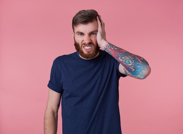 Photo of young attractive tattooed red bearded man in blank t-shirt, feels a strong headache and touches head, stands over pink background and bares his teeth.