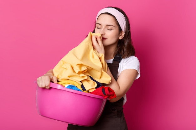 Photo of young attractive woman working at home, wears t shirt, brown apron and hair band, standing with pink basin with clean linen isolated on rose wall in photo studio, smells fresh clothes.