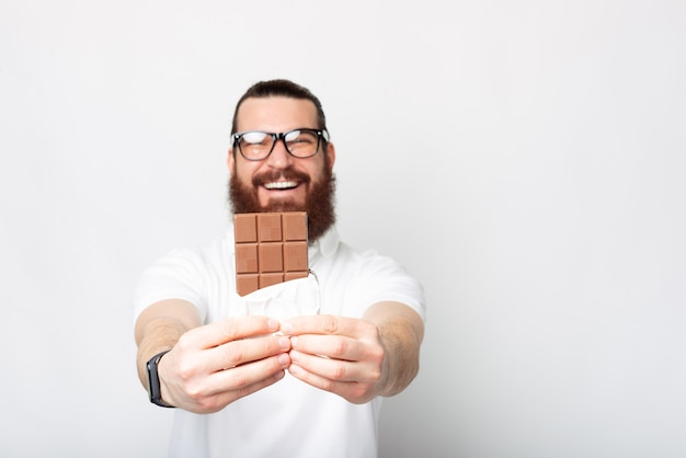 A photo of a young bearded man cheerful holding a chocolate bar near a white wall
