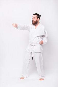 Photo of young bearded man in dobok uniform practicing taekwondo over white wall