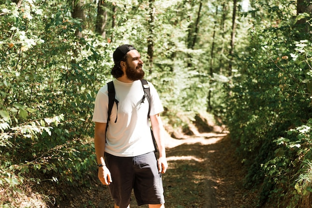 Photo of young bearded man hiking in forest during summer time, travel concept.
