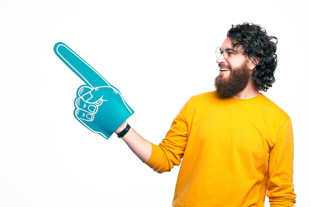 Photo of young bearded man pointing at copyspace over white background