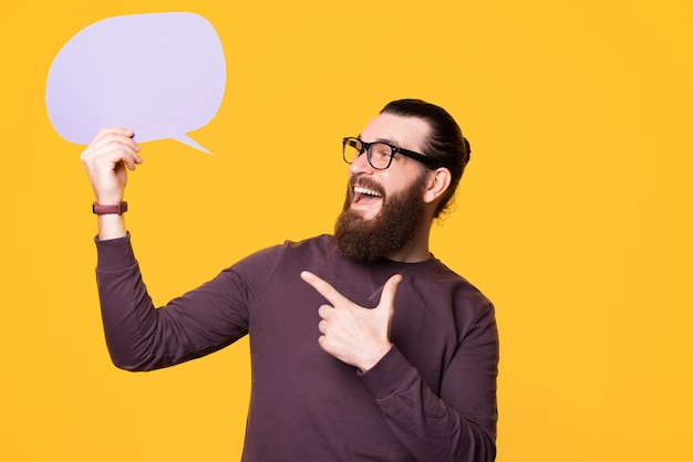 Photo of a young bearded man pointing at a speech bubble that he is holding near a yellow wall wearing glasses