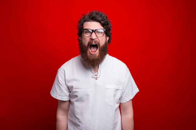 Photo of young bearded man screaming and looking at the camera