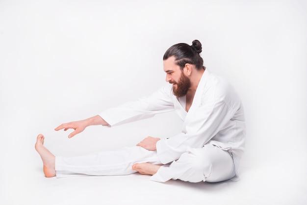 Photo of young bearded man wearing taekwondo uniform making stretching over white wall