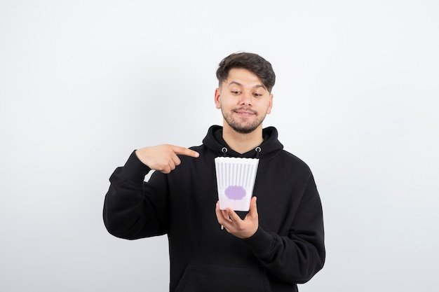 Photo of young beautiful man watching television series and holding popcorn bucket