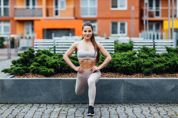 Photo of young beautiful sportswoman outdoor doing exercises in the city.