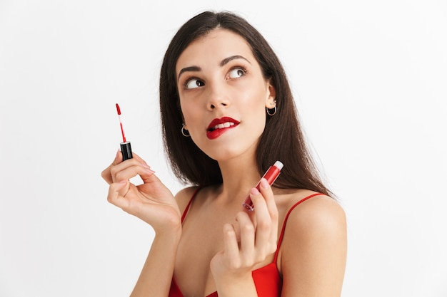 Photo of young beautiful woman posing isolated holding lip gloss doing makeup.