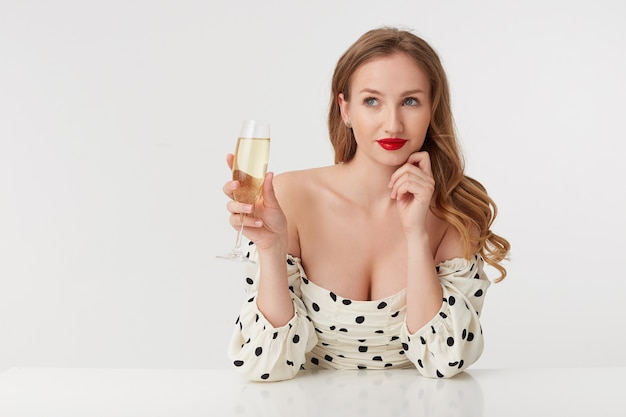 Photo of young beautiful woman with long blond hair and red lips, leaning on the arm, thinks about her lover, smiles wistfully isolated over white wall.