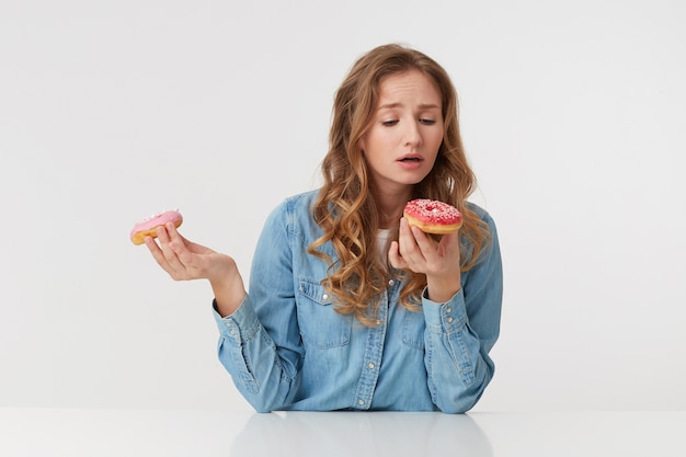 Photo of young beautiful woman with long blond wavy hair, wearing a denim shirt, holds donuts in her hands, gonna bite one of them. isolated over white background.