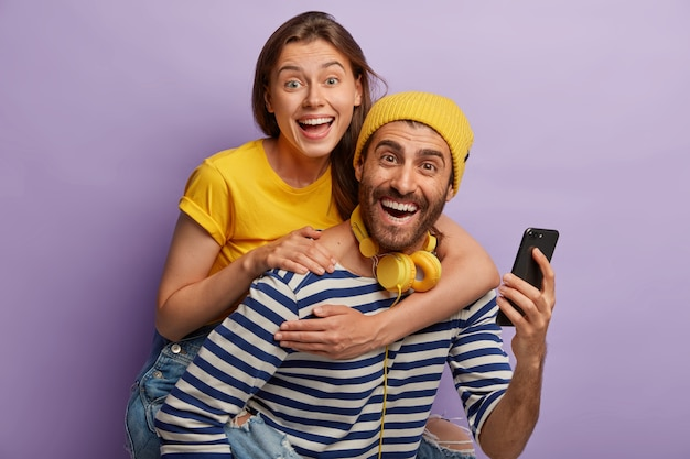 Photo of young boyfriend and girlfriend have fun together, man gives piggyback ride to female, use mobile phone, laugh joyfully, isolated over purple wall. happy bloggers