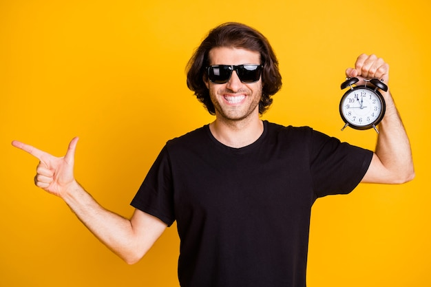 Photo of young bristled man indicate direct finger empty space hold alarm clock show time t-shirt sunglass isolated yellow color background