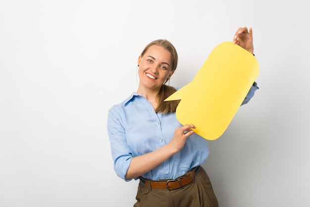 Photo of young business woman in casual holding empty yellow speech bubble with free space for text