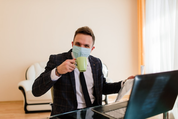 Photo of young businessman with notebook freelance job internet, want get job quarantine stay home, wear facial medical mask