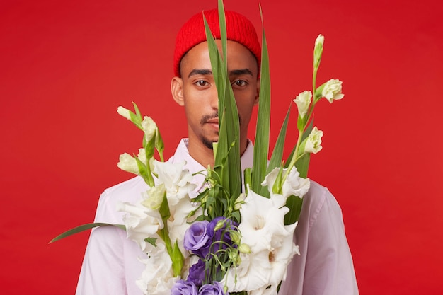 Photo of young calm dark skinned man, wears in white shirt and red hat, looks at the camera trough bouquet , stands over red background.