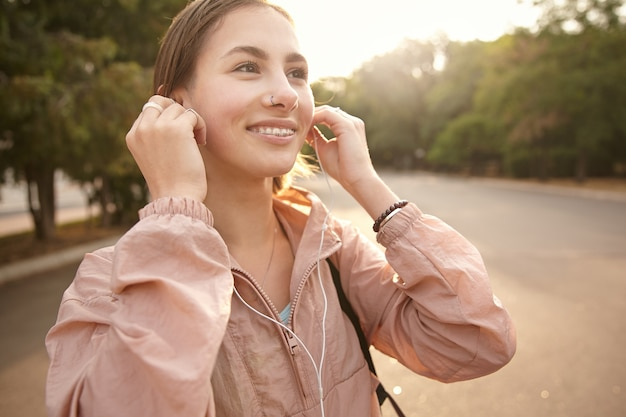 Photo of young cheerful woman walking at the park, listening favorite soundtrack in headphones, broadly smiling and looks away, enjoy the sunny day.