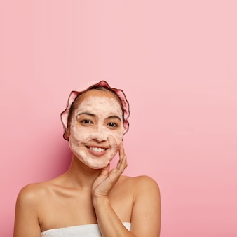 Photo of young chinese woman enjoys purification os face skin, washes with soap, touches cheek, looks with smile , clean pores, wears bath cap, poses indoor, copy space on pink wall